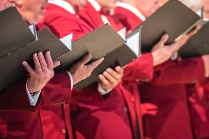 A choir holding music folders