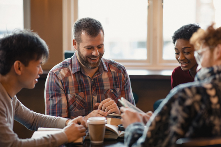 three men and a woman with notebooks and coffee cups sit at a table laughing
