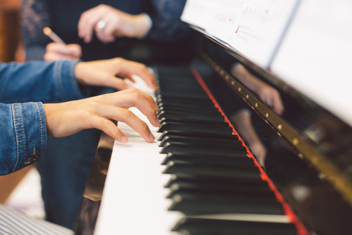 Close up for a student's hands on a piano keyboard with a teacher's hands in the background.