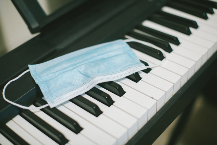 A disposable surgical mask is laid across a piano's keys.