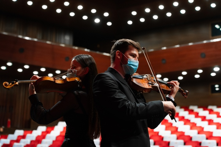 masked string musicians playing in empty concert hall