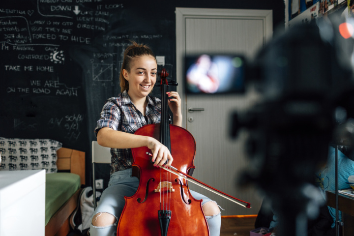 girl playing cello with camera