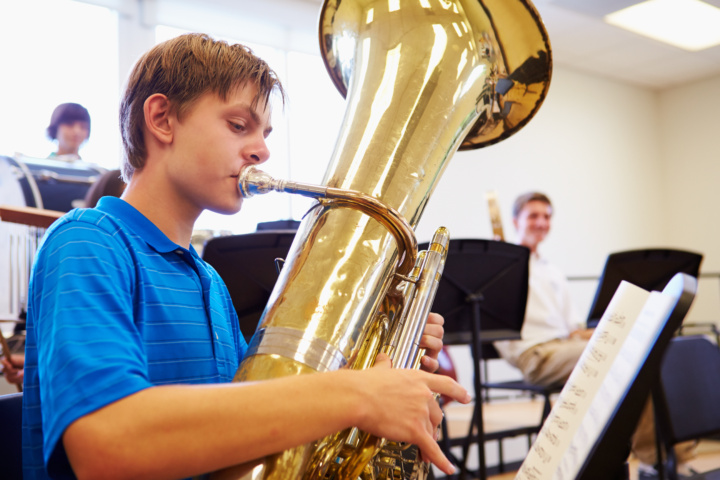 Boy holding trombone in a music lesson