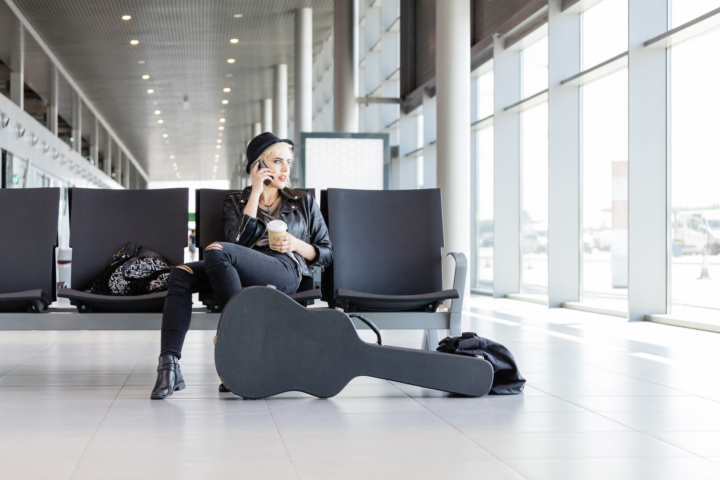woman at airport with guitar