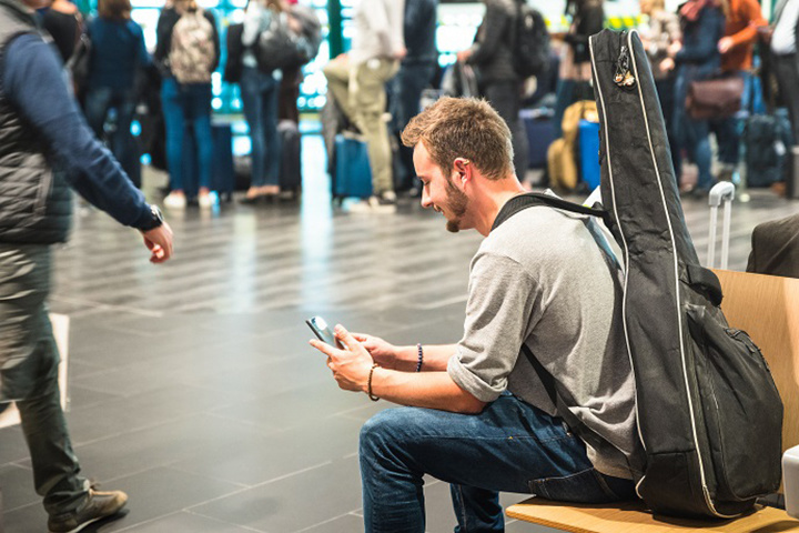 ,man with guitar at airport