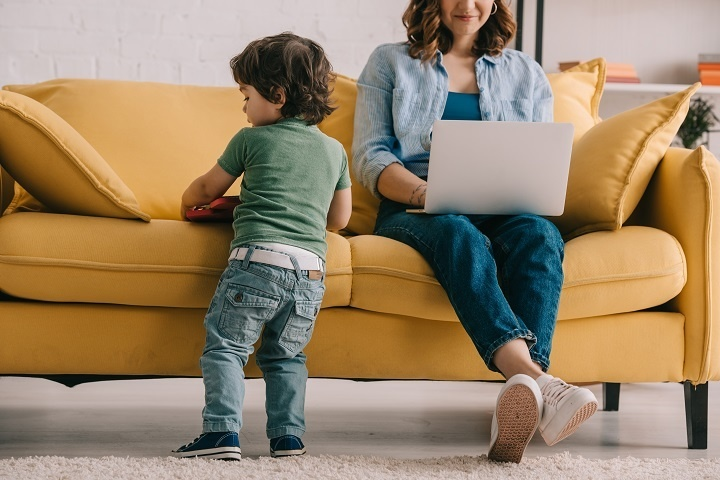 WOMAN ON LAPTOP ON SOFA WITH TODDLER