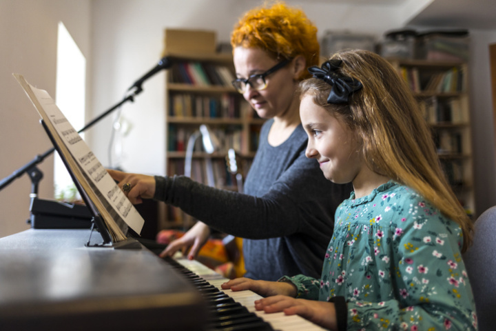 Young girl having piano lesson