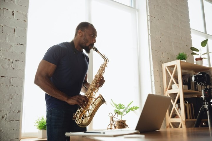 Man plays his saxophone in front of a laptop