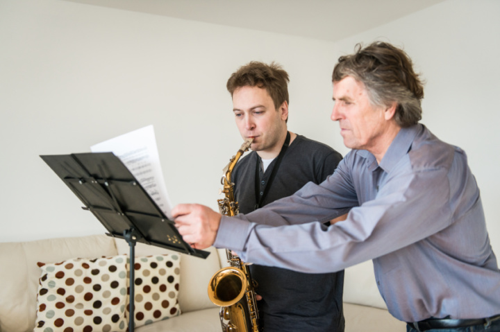 A teacher is directing his male saxophone student and turning the pages of his music for him while he plays.