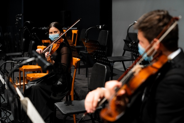 Socially-distanced masked violinists look towards each other