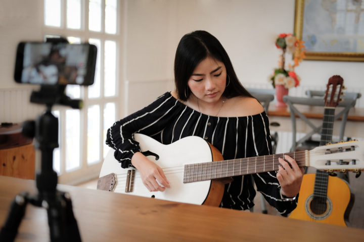 Woman plays guitar to a camera set up on a table