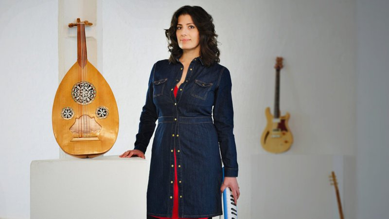 Bushra stands with her instruments around her
