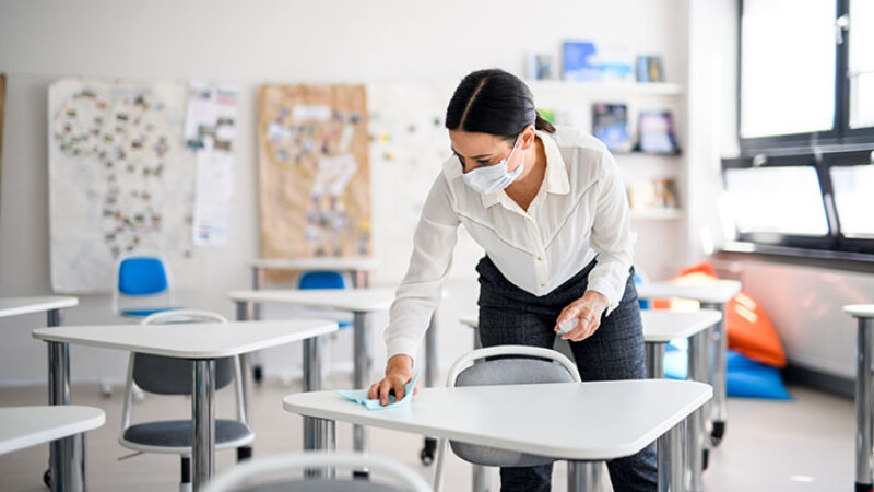 A female teacher wipes a desk
