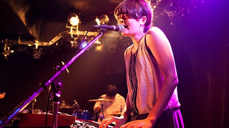 In the foreground, a young female musician singing and playing keyboard on stage.  A drummer is playing in the background.