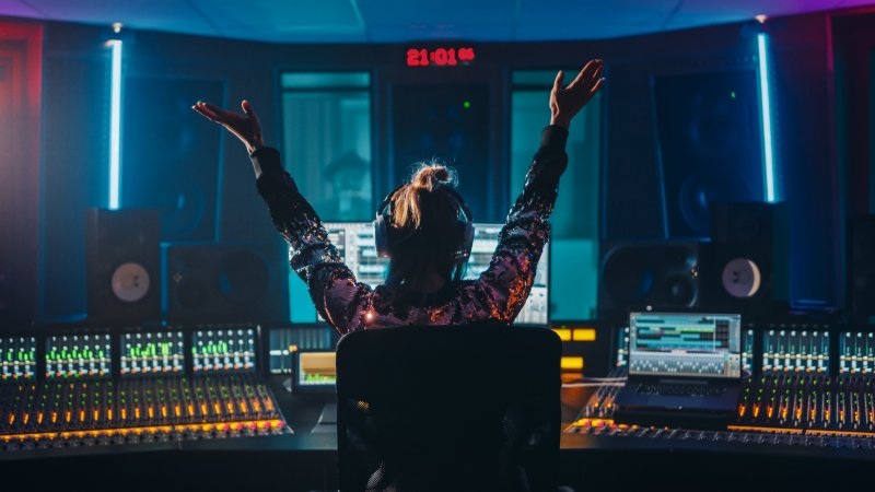 A woman sits with her arms raised in a studio, surrounded by a mixing desk and laptops.